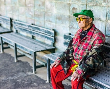 An old man on a park bench dressed like a teenager